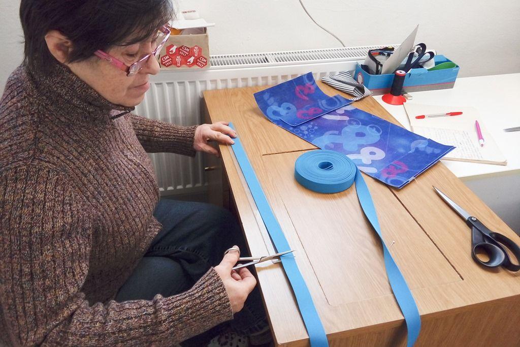 Paní Marie všicí dílně připravuje gumy pro obaly naknihy Etnetera